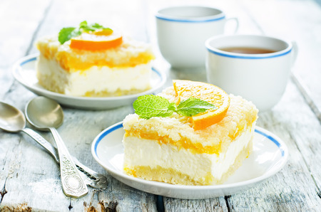 cake with orange, cream cheese and crumbs on a light woody background. tinting. selective focus on mint