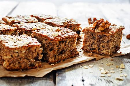pastel: pastel de harina de avena con las fechas y las nueces en un fondo de madera oscura. tintado. enfoque selectivo en la nuez Foto de archivo