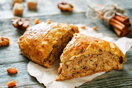 walnut cake: pumpkin scones with cinnamon, raisins and walnuts on a dark wood background. tinting. selective focus Stock Photo