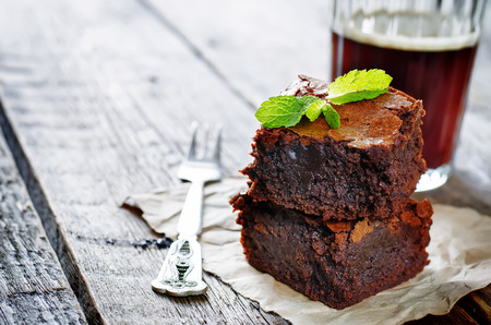 chocolate brownie: brownie on a dark wood background. tinting. selective focus on mint