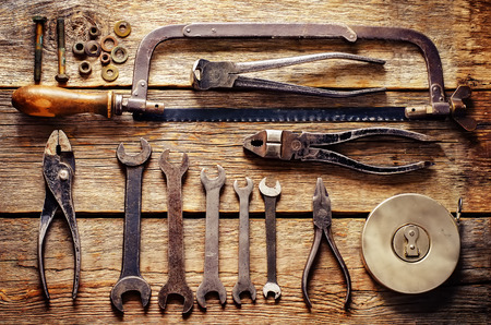 old tools, wrenches on a dark wood background. tinting. selective focus on the middle tool photo