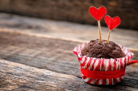 chocolate muffins on dark wood background for Valentine's day. tinting. selective focus