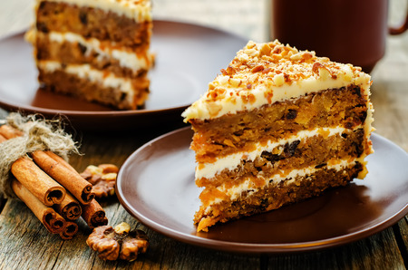 carrot cake with walnuts, prunes and dried apricots on a dark wood background. tinting. selective focus