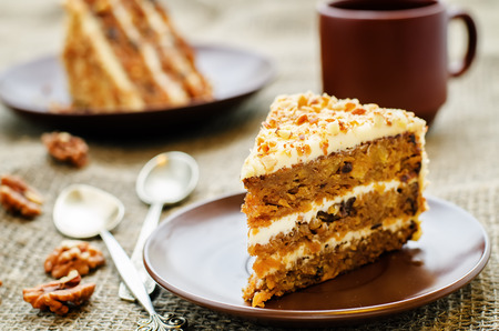 carrot cakes: carrot cake with walnuts, prunes and dried apricots on a dark background. tinting. selective focus