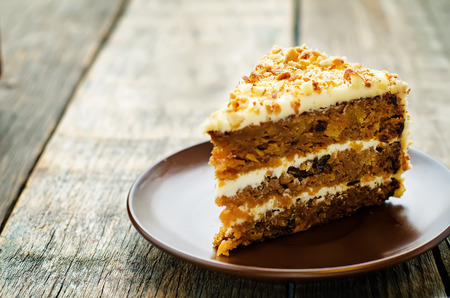walnut cake: carrot cake with walnuts, prunes and dried apricots on a dark wood background. tinting. selective focus