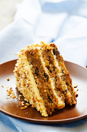 tort: carrot cake with walnuts, prunes and dried apricots on a dark wood background. tinting. selective focus