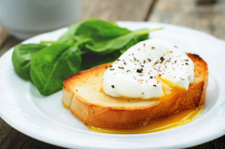 huevos revueltos: huevo escalfado con espinacas en un fondo de madera oscura. tintado. enfoque selectivo Foto de archivo