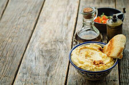 hummus on a dark wood background. Stock Photo