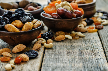 mix of dried fruits and nuts on a dark wood background. tinting. selective focus