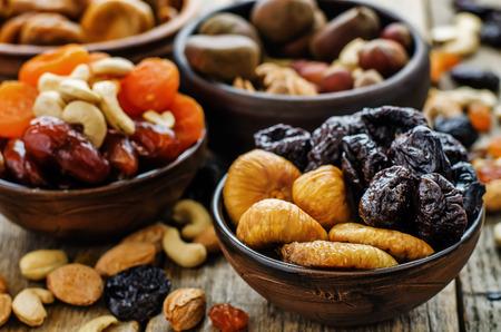 comida sana: Mezcla de frutas secas y nueces sobre un fondo de madera oscura. tintado. enfoque selectivo