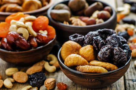 vegetarian food: mix of dried fruits and nuts on a dark wood background. tinting. selective focus