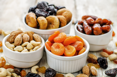comida arabe: Mezcla de frutas secas y nueces sobre un fondo de madera blanca. tintado. enfoque selectivo