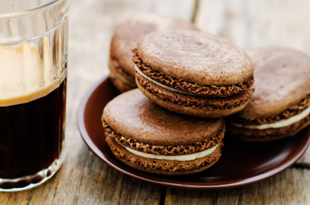 tinting: chocolate macaron with cream cheese and coffee on a dark wood background. tinting. selective focus