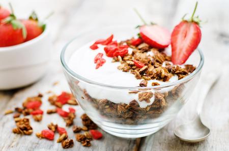 fresh cream: fresh breakfast of granola, yogurt, nuts, goji berries and strawberries. tinting. selective focus