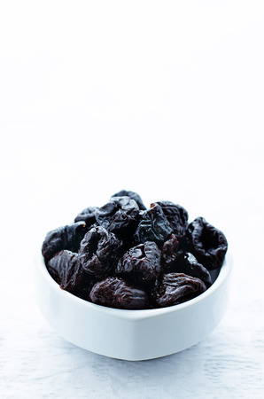 tinting: prunes in a bowl on a white background. tinting. selective focus
