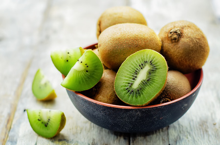 kiwi on white wood background. tinting. selective focus Фото со стока