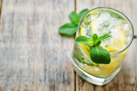 lemonade: limonada con menta sobre un fondo de madera oscura. tintado. enfoque selectivo