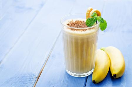 banana: banana milkshake on a blue wood background. tinting. selective focus