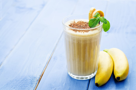 banane: milk-shake banane sur un fond de bois bleu. coloration. mise au point s�lective
