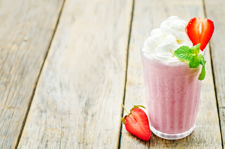 strawberry milkshake with whipped cream on a dark wood background. tinting. selective focus Standard-Bild