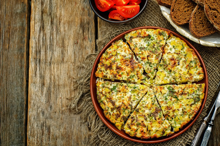 tinting: Frittata with chicken and potatoes on a dark wood background. tinting. selective focus Stock Photo