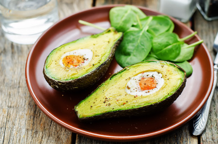 avocado baked with egg on a dark wood background. tinting. selective focus