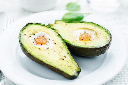 huevo: aguacate al horno con huevo sobre un fondo blanco. tintado. enfoque selectivo