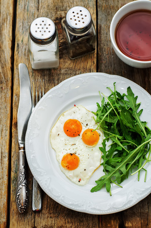fresh breakfast with scrambled eggs and arugula on a dark wood background. tinting. selective focus Stock Photo - 37164953