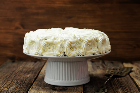 calorie rich food: cake with vanilla cream in the form of roses on a dark wood background. tinting. selective focus Stock Photo