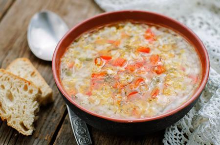 arroces: sopa de pollo con arroz y pimientos sobre un fondo de madera oscura. tintado. enfoque selectivo