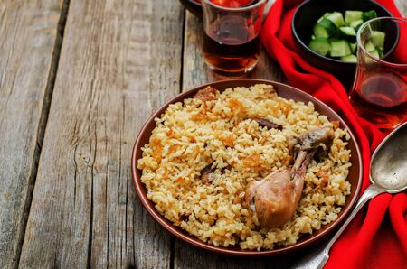 pilaf with dates, figs and chicken on a dark wood background. tinting. selective focus