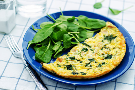 scrambled: Frittata with chicken and spinach and fresh spinach on a light background. tinting. selective focus