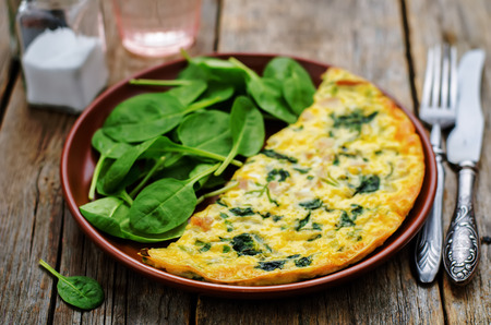 Frittata with chicken and spinach and fresh spinach on a dark wood background. tinting. selective focus