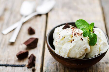 cream color: vanilla ice cream with chocolate topping on a dark wood background. tinting. selective focus