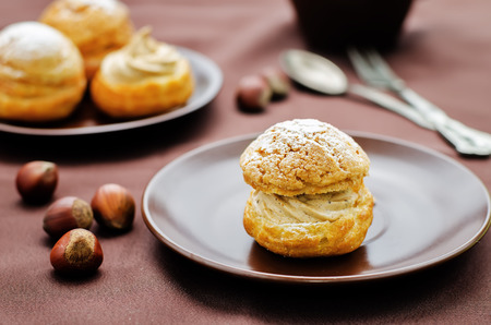 profiterole: profiteroles with cream with praline on a brown background Stock Photo
