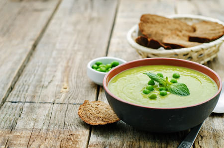 hot soup: soup puree of green peas on a dark wood background. tinting. selective focus