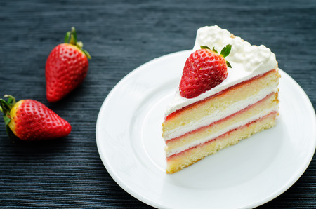 cake with cream and strawberries on a dark background. tinting. selective focus