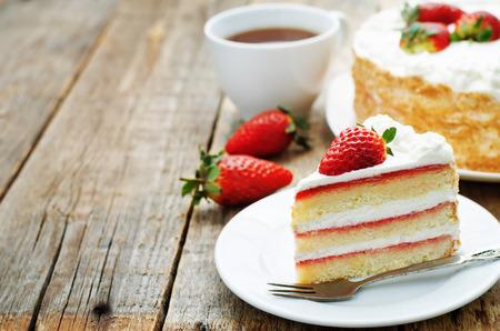 porcion de torta: pastel con crema y fresas sobre un fondo de madera oscura. tintado. enfoque selectivo
