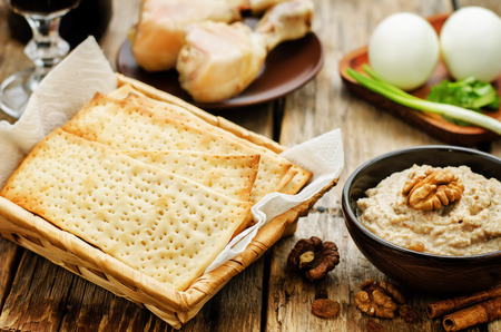 matzah: Matzah, wine, eggs, chicken, greens and haroset on a dark wood background, traditional food for the Pesach. tinting. selective focus