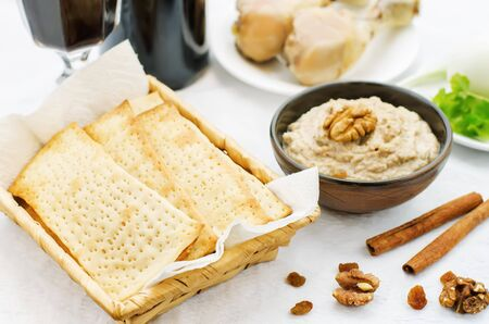 matzah: Matzah, wine, eggs, chicken, greens and haroset on a white background, traditional food for the Pesach. tinting. selective focus Stock Photo