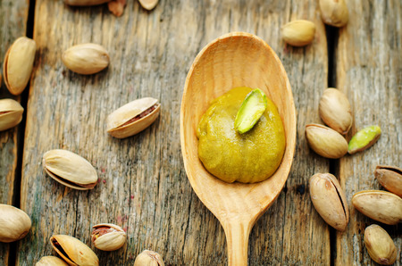 pistachio paste on a dark wood background. tinting. selective focus