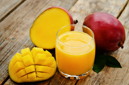 natural juices: mango juice and fresh mango on a dark wood background. tinting. selective focus