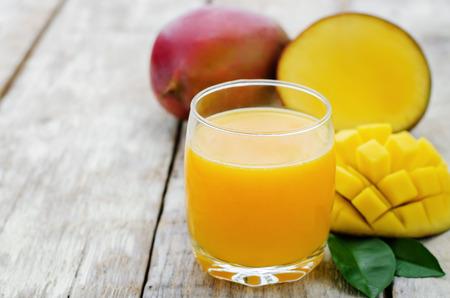 mango fruta: jugo de mango y mango fresco en un fondo de madera blanca. tintado. enfoque selectivo