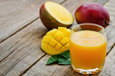 vaso de jugo: jugo de mango y mango fresco en un fondo de madera oscura. tintado. enfoque selectivo