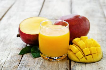 mango: Sok z mango i świeże mango na białym tle drewna. barwienia. selektywne focus