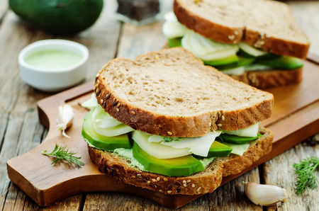 sandwiches with avocado, cheese, cabbage and cheese and herb topping. tinting. selective focus Фото со стока