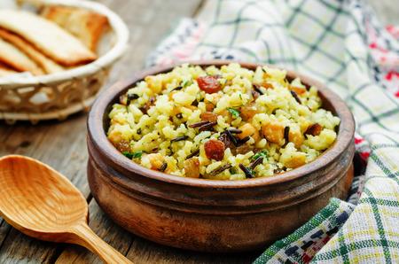 berenjena: arroz, arroz salvaje, garbanzos con pasas y hierbas en un fondo de madera oscura. la tonificaci�n. enfoque selectivo
