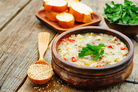 delicious: milk soup with potatoes, quinoa and peppers on a dark wood background. the toning. selective focus Stock Photo
