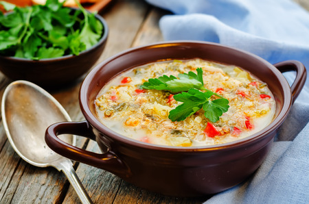 milk soup with potatoes, quinoa and peppers on a dark wood background. the toning. selective focus Banco de Imagens