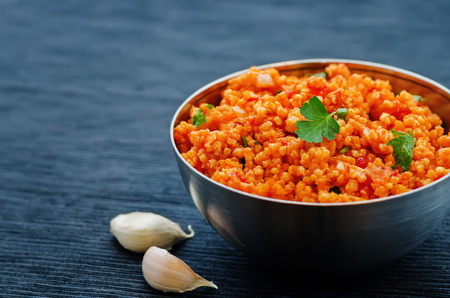 mediterranean food: millet porridge with tomato sauce, garlic and parsley on a black background. the toning. selective focus Stock Photo